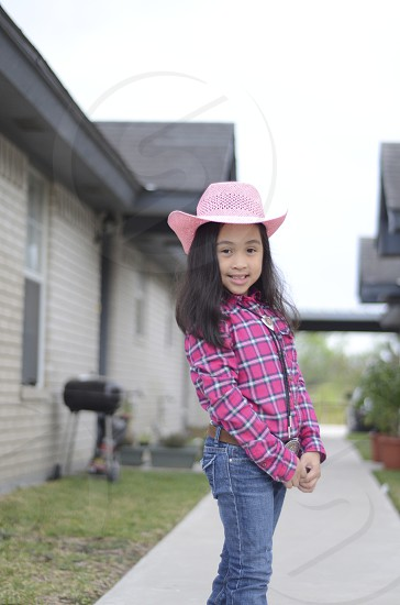girl in pink cowboy hat standing photo