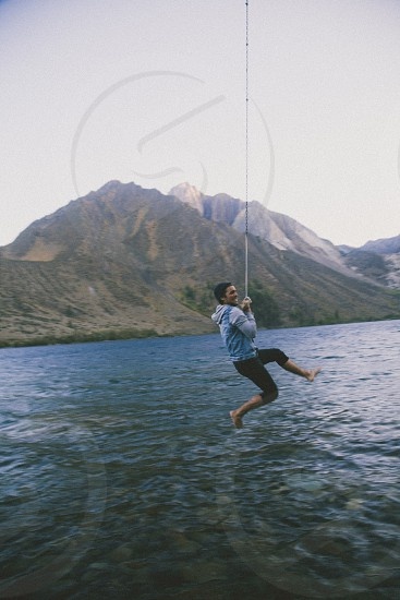 man in blue sweatshirt black pants seining on rope over lake and mountains photo