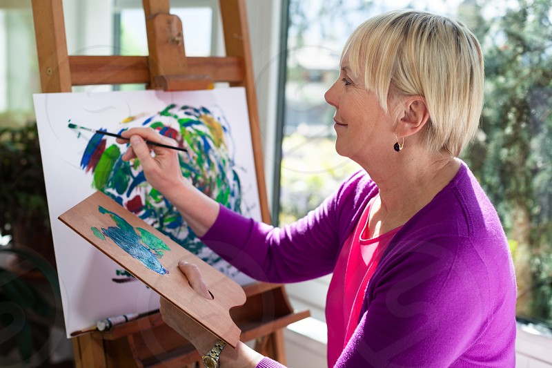 painter; painting; palette; hobby; retired; senior; woman; 50s; 60s; activity; aged; alone; art; artist; artistic; artwork; blonde; brush; canvas; caucasian; creativity; domestic; easel; elderly; enjoyment; female; free time; grandma; grandmother; happiness; happy; hobbies; home; indoors; inspiration; leisure; lifestyle; modern; old; one; paint; paintbrush; pensioner; people; person; relaxation; retirement; serene; sitting; white photo