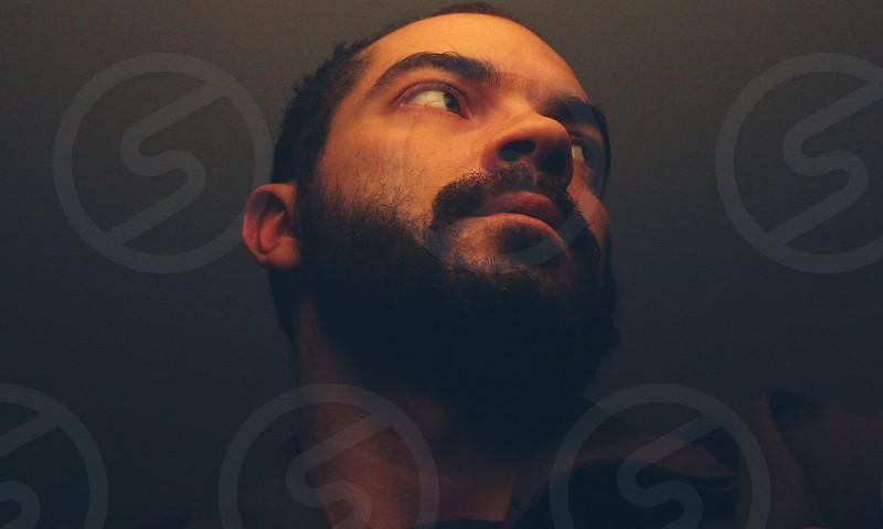 Bearded man portrait in a dark room photo