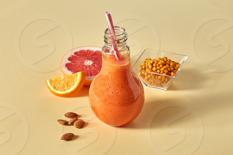 Fresh smoothies with carrots orange grapefruit almonds and sea-buckthorn in a glass on a paper orange background.The vitamin drink concept photo