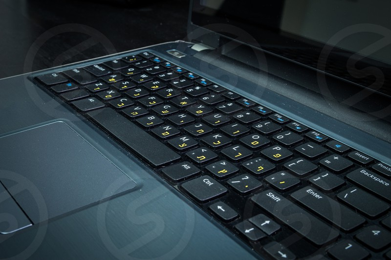Keyboard with letters in Hebrew and English - Laptop keyboard - Dark atmosphere photo
