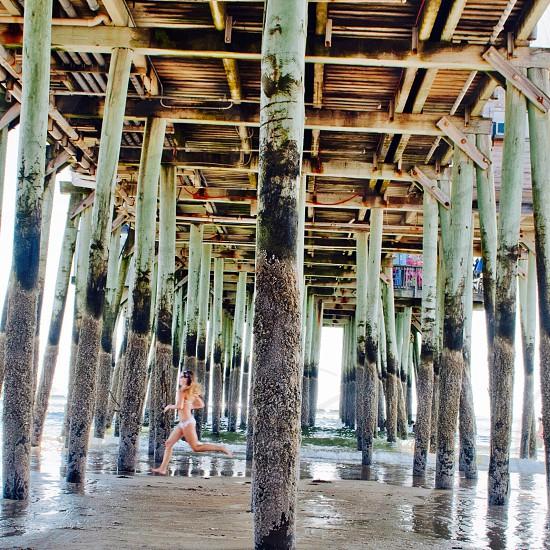 woman running under wooden pair photo
