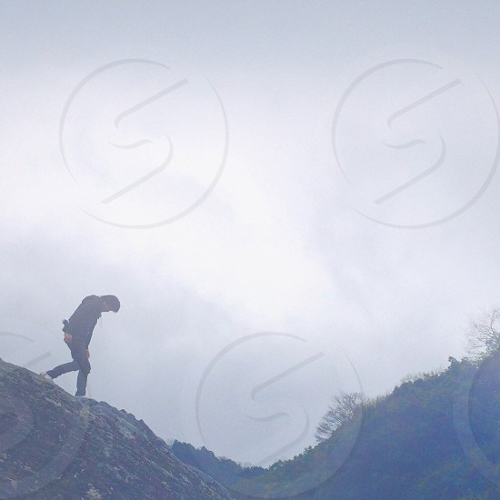 man in white shoes walking on hill photo