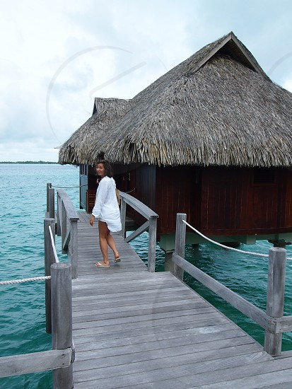 woman standing in front of black wooden house photo