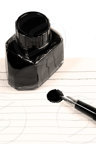 classic black fountain pen on open notebook with ink bottle with stain on pagesepia filter photo