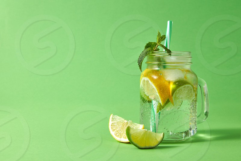 Summer refreshing drink on a green background. Homemade sparkling cocktail with ice slices of lime and lemon green leaves of mint with plastic straw in glass jar. photo