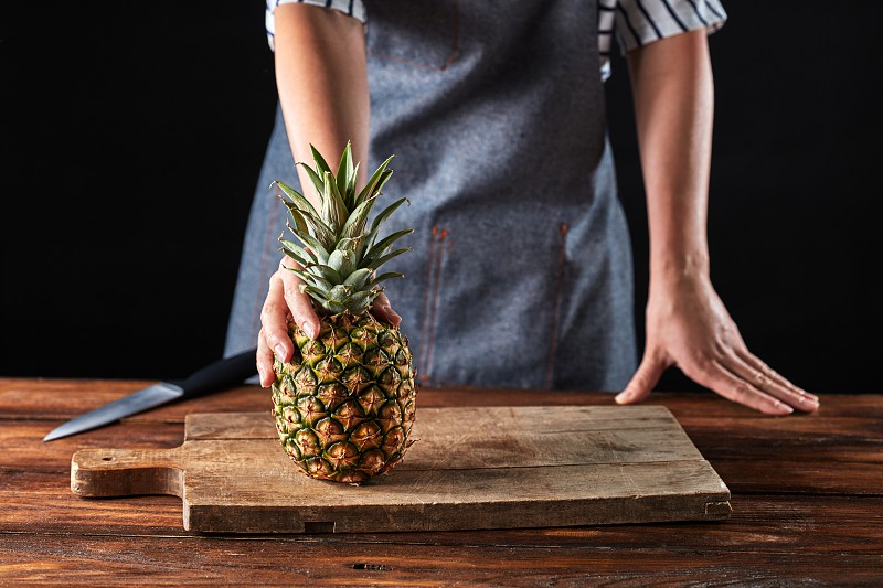 A girl in an apron holds organic pineapple on a wooden board on a brown table around a dark background with copy space. Ingredient for dessert photo