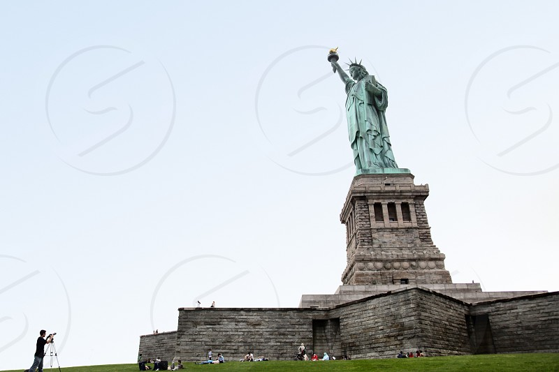 A photographer composes a shot of the statue of liberty. photo