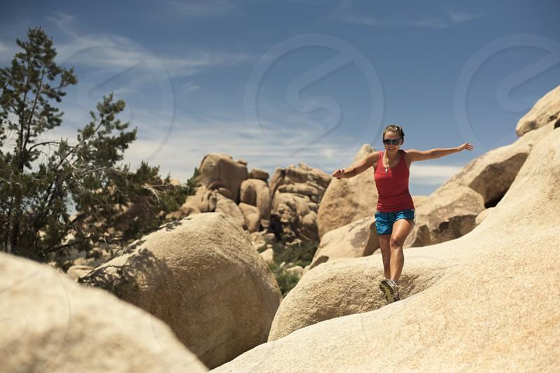 Woman running rocks joshuatree national park photo
