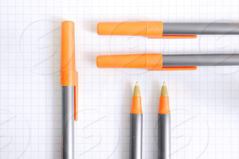 silver pens with orange caps on graph paper photo