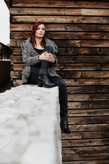 Beautiful girl seating on concrete wall in front of wooden wall looking in the distance. photo