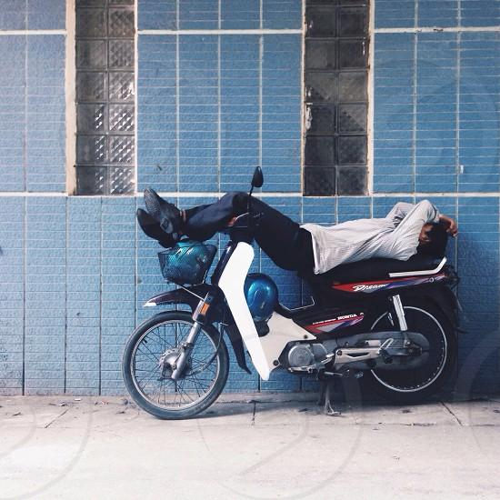 person lying on Honda dream motorcycle photo