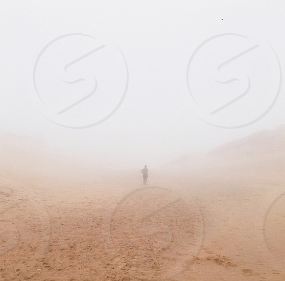 person standing on brown sand beach photo