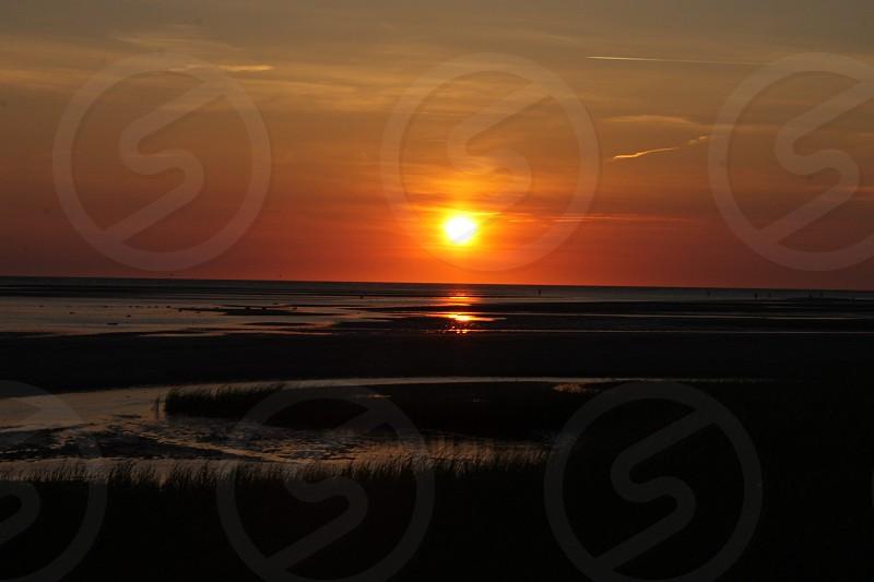 orange sun over dark large body of water photo