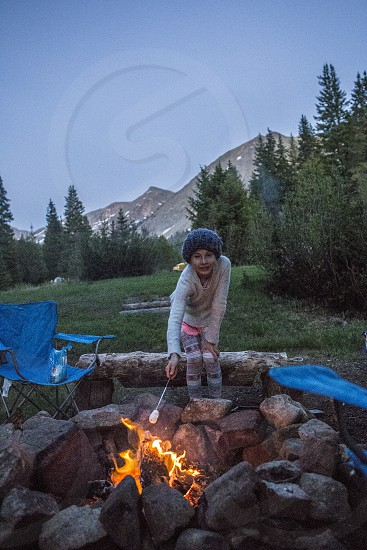 little girl roasting marshmallow and camping photo
