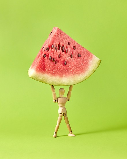 Miniature wooden human mannequin holds fresh ripe sweet watermelon's part on a lawn green background with soft shadows copy space. photo