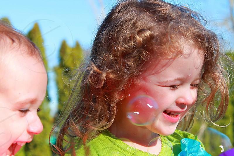children blowing bubbles photo