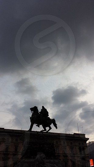 silhouette on man of horse on top of building under nimbus clouds photo