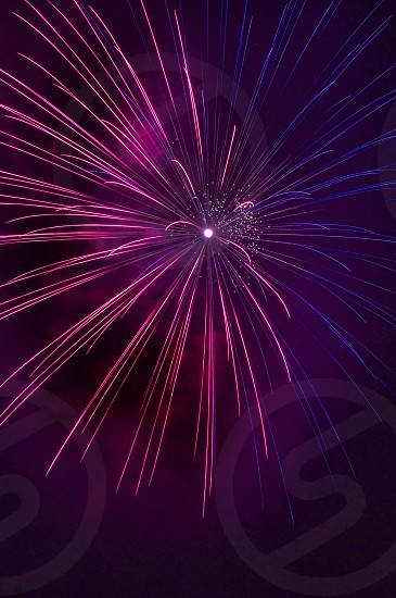 pink and blue fireworks explode at the sky photo