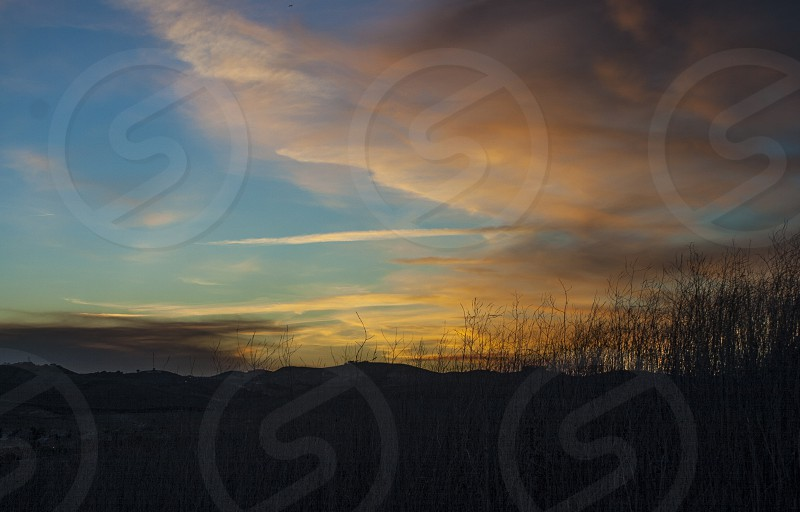 sunset and clouds over hills photo