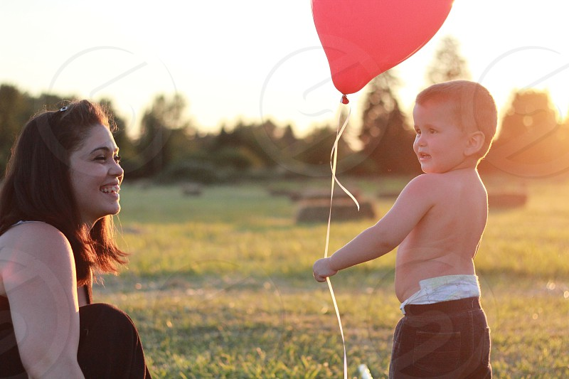 child holding red balloon standing outdoors photo