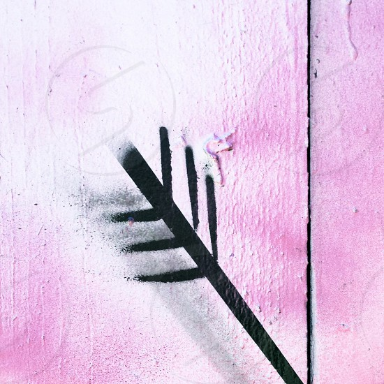 Graffiti of arrow in pink wall photo