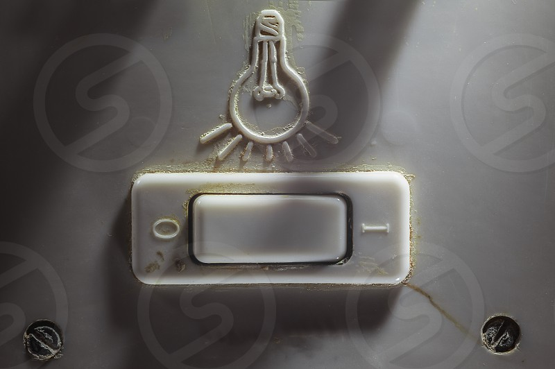 Details of an old dirty plastic switch for turning light on or off.  photo