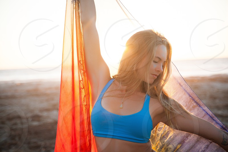 woman in blue sportsbra holding sheer orange cloth up on sunny beach photo