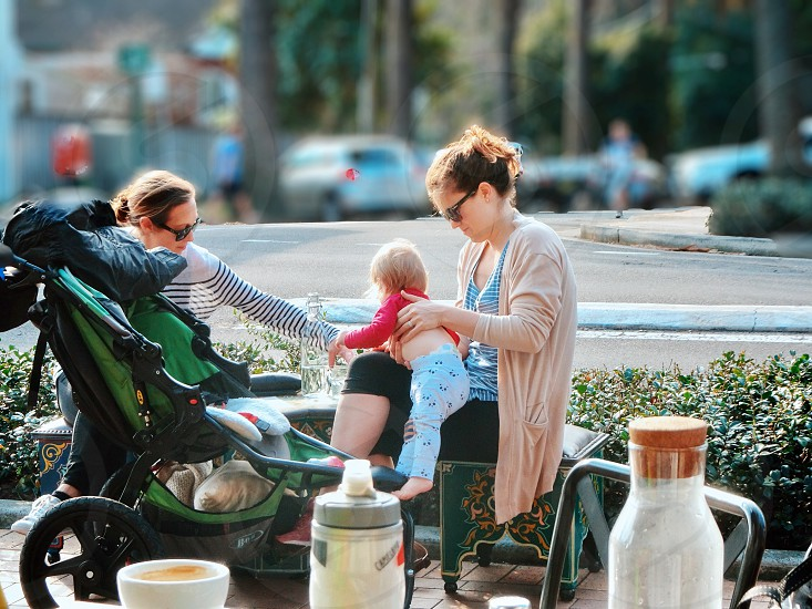 Motherhood mom baby mother coffee cafe lifestyle outdoors natural light girlfriends talking cafe lifestyle daily life candid real life morning routine coffee break toddler active baby photo