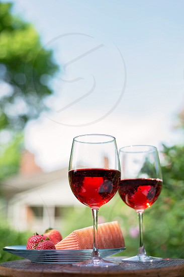 wine rose 2 glasses outdoor dining natural light garden strawberries cheese pink beverages  photo
