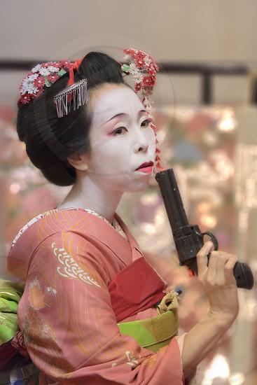 Pretty young Geisha maiko girl in kimono holding a plastic gun in her hand. photo