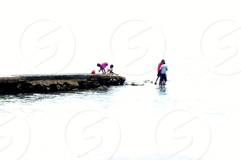 Children fishing from an old pier. photo