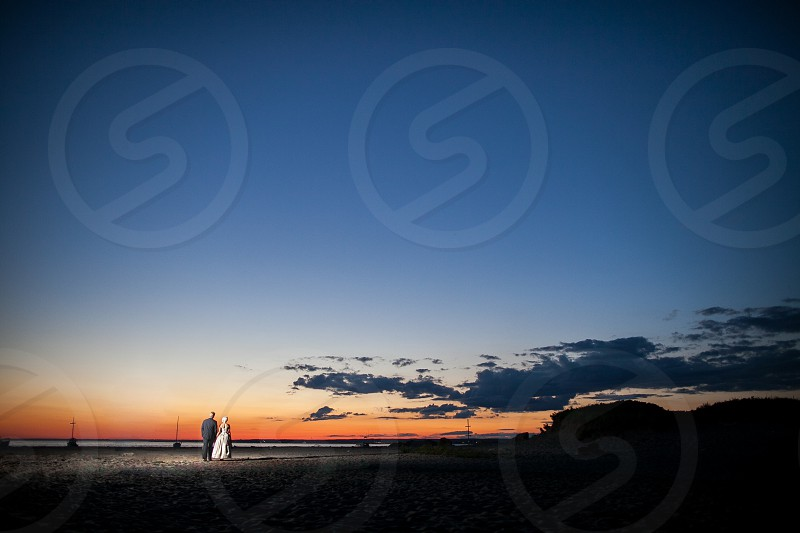 A bride and groom walking on the beach during sunset. Sky blue sand clouds coast water ocean photo
