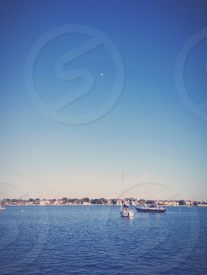 sailboats on water with land in distance under sunny sky photo