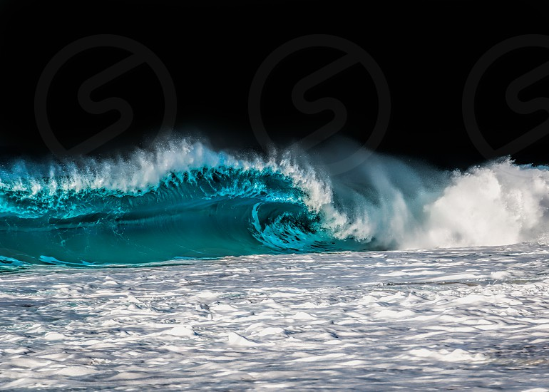 Crystal clear wave with a black backdrop. Photo taken on the Northshore of Oahu photo