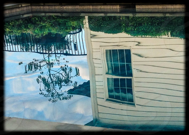 white wooden house and green trees water reflection photo