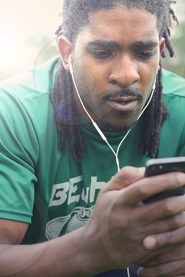 man in green crew neck t-shirt holding black smartphone and wearing white earphones photo