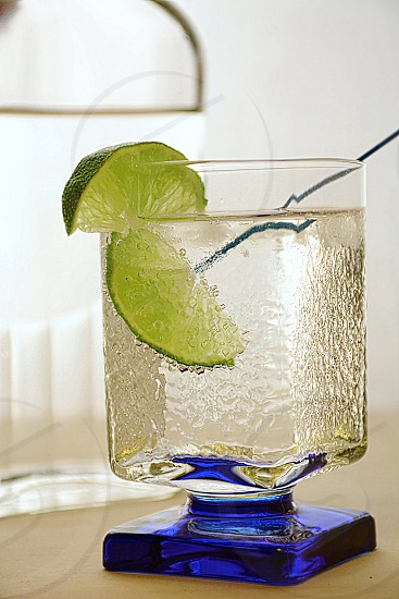 Close-up image of an elegant glass a gin and tonic with lime wedges. Clear bottle behind the glass. photo