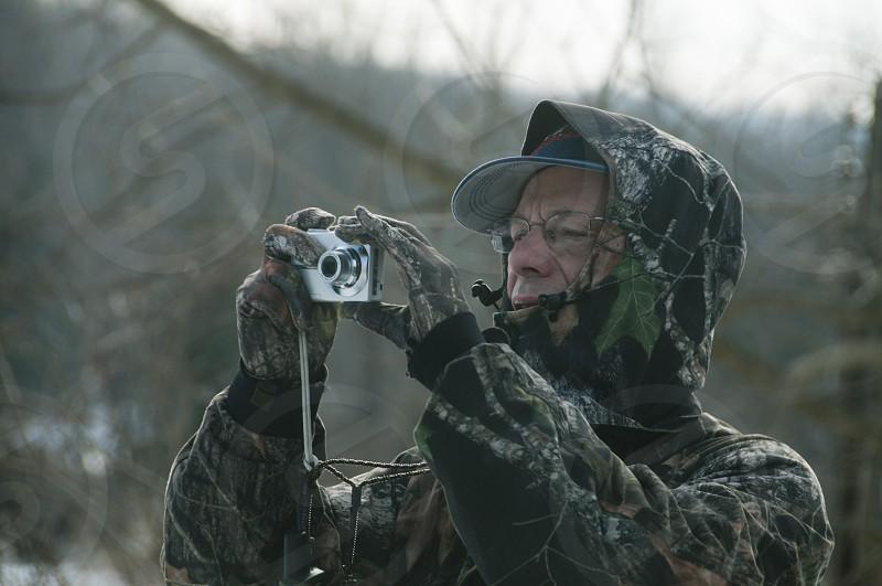 man wearing cap taking pictures photo