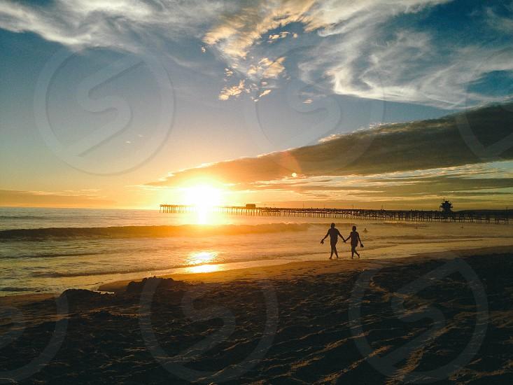 man and woman silhouette along the seashore photo