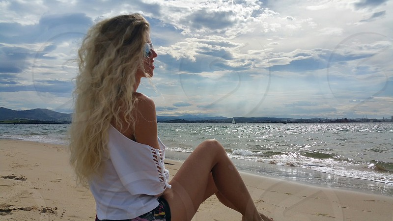 Blonde girl sitting on the beach and looking on the ocean photo