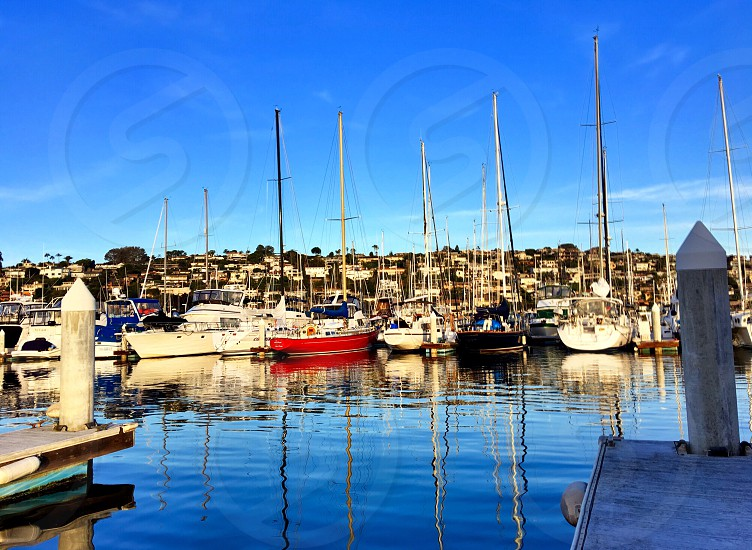 Boating Lifestyle Colorful Sailboats and Motorboats in the Harbor with Reflections of the Masts on the Water sailboats Harbor reflections  photo