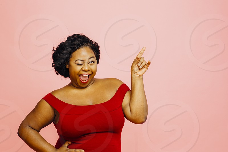 Portrait of a sexy voluptuous woman smiling winking and pointing up isolated on pink studio background photo