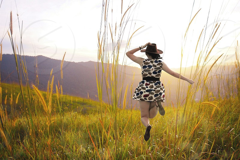 woman in black white sleeveless mini dress and black cowboy hat running across brown grass during daytime photo