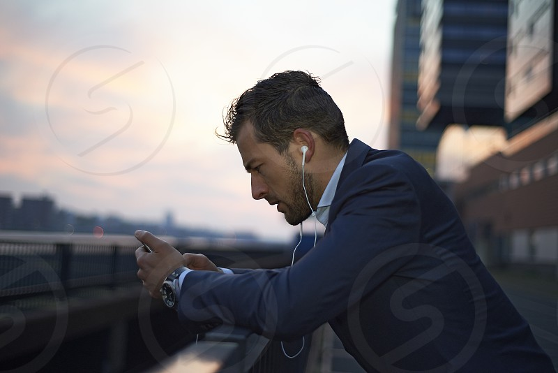 Side profile of a business man using his mobile phone wearing ear phones in early morning sunrise photo