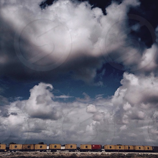 cumulonimbus clouds over red and yellow train photo