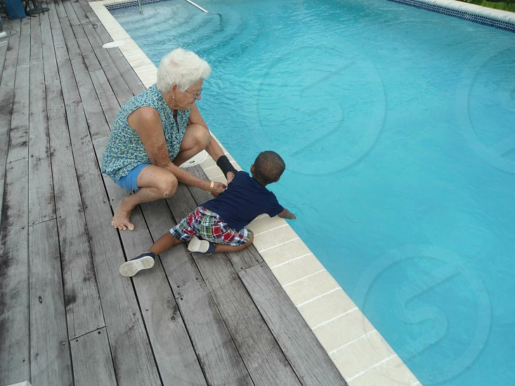 Grandma watches over her grandson at the pool side on the beautiful island of St Lucia photo