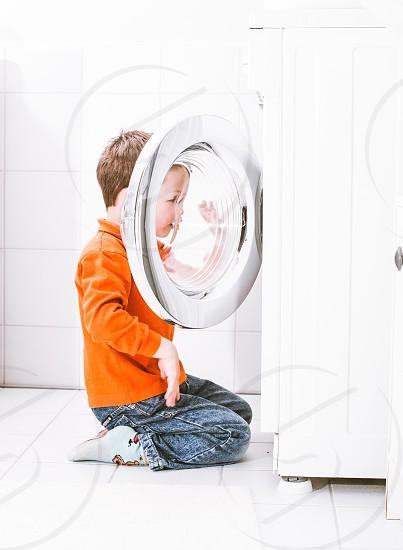 boy play washing machine bathroom lifestyle photo
