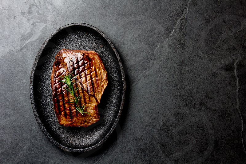 Grilled beef steak on black cast iron plate. Background with copy space. Barbecue bbq meat beef tenderloin. Top view slate background. photo